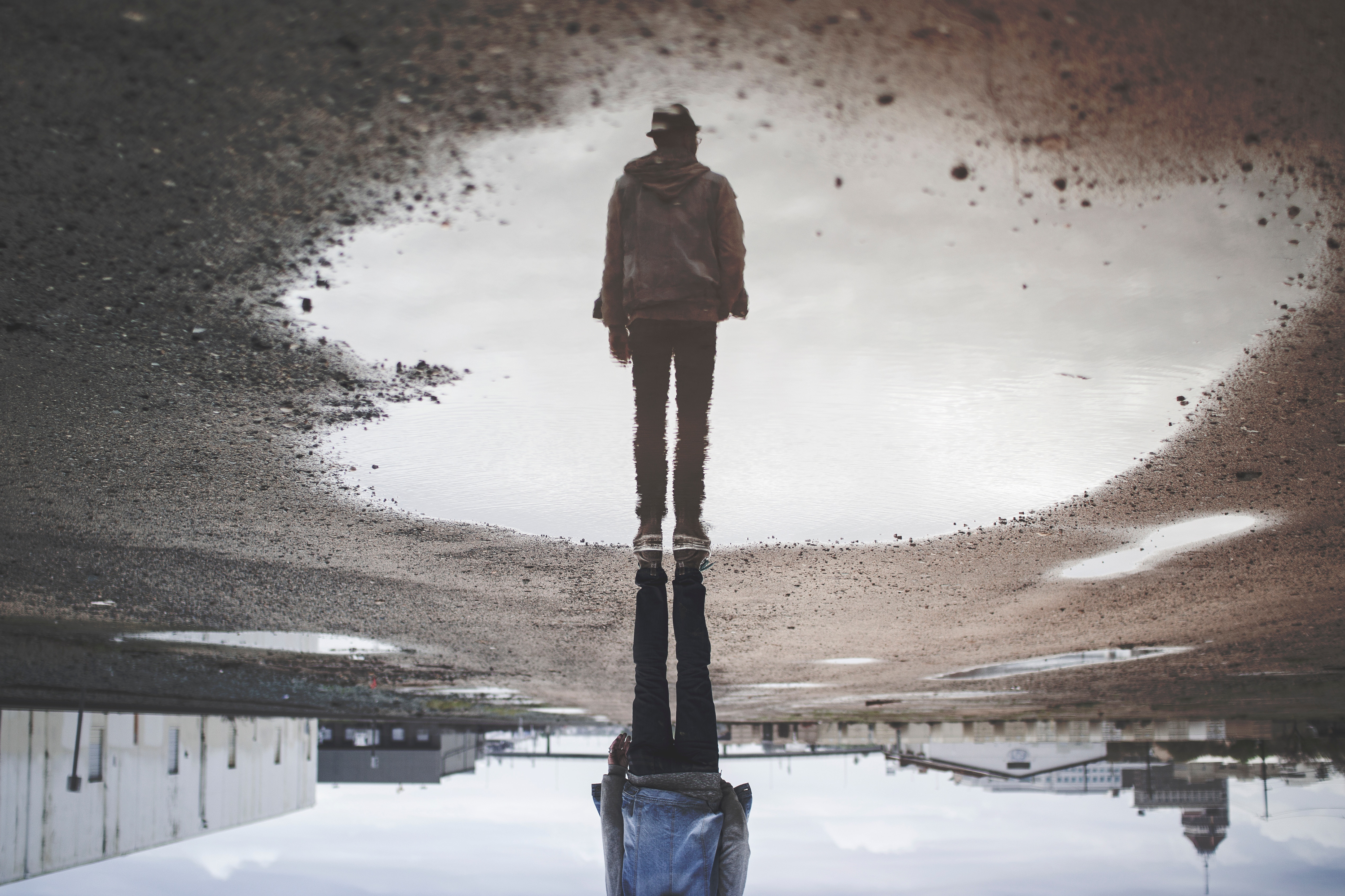 Man standing by puddle with reflection